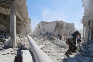 Residents inspect damage at a site hit by what activists said were barrel bombs dropped by forces of Syria's President Assad in Aleppo